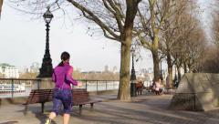 Tourists and a jogger along the Southbank of the Thames Stock Footage