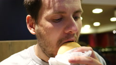 Hungry young man greedily eating hamburger and french fries in fast food Stock Footage