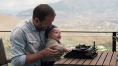 Young father showing typewriter to his small son while sitting on terrace HD Stock Footage