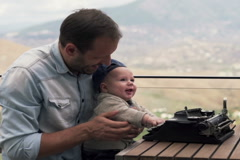 Young father showing typewriter to his small son while sitting on terrace  NTSC - stock footage