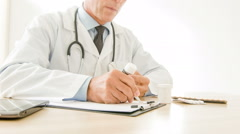 Doctor writing down medical prescriptions - stock footage