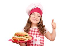 Happy little girl cook with hot dog and thumb up Stock Photos