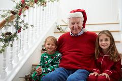 Grandfather With Grandchildren Sits On Stairs At Christmas Stock Photos