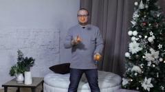 Man juggle mandarins near christmas tree Stock Footage