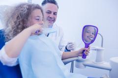 Pediatric dentist teaching girl how to brush teeth Kuvituskuvat