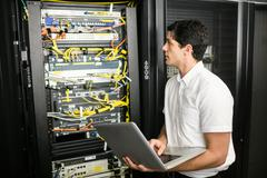 Technician using laptop to analyse server Stock Photos