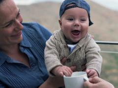 Cute small baby sitting on the mother's knees and playing with mug NTSC Stock Footage