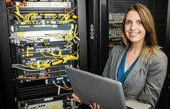 Technician using laptop to analyse server Stock Photos