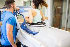 Woman using an anti gravity treadmill beside trainer - stock photo