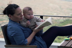 Mother trying read book while sitting on the terrace with her little son NTSC Stock Footage
