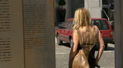 Woman reading the inscriptions at the Monument for Freedom of Speech in Warsaw Stock Footage