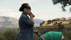 Young, pretty mother answer phone calls during walk with her son HD Stock Footage