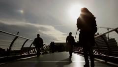 Silhouetted people on Millennium Bridge walking towards Tate Modern Stock Footage
