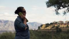 Young attractive woman talking on cellphone in the country with mountain view HD Stock Footage