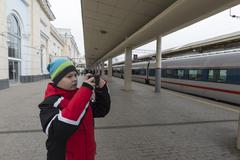 sad teenager boy standing near train and photographs on smartphone - stock photo