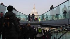 People on different levels of the Millennium Bridge with St Pauls in background - stock footage