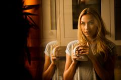 Pretty woman drinking coffee in the kitchen Stock Photos