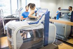 Stock Photo of Woman using an anti gravity treadmill beside trainer
