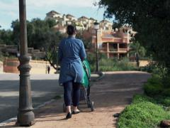 Young mother walking with perambulator in the small city NTSC Stock Footage