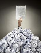 Hand with agreement reaches out from heap of papers - stock photo