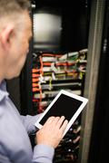 Technician using tablet pc while analysing server Stock Photos