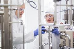 Stock Photo of Scientists working with large vat