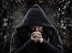 Despair bandit praying God for forgiveness Stock Photos