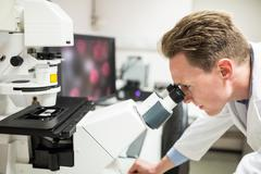 Scientist looking through a microscope Stock Photos