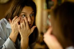 Young woman putting in contact lens Stock Photos