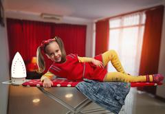 Happy little girl lying on the ironing-board smiling Stock Photos