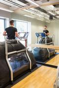 Injured athlete working out on treadmill Stock Photos