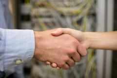 Technicians shaking hands in server room Kuvituskuvat