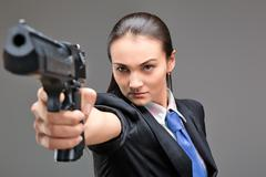 Young caucasian woman holding gun in her hand Stock Photos