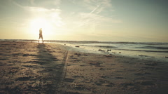 Man walks on beach during sunset, graded - stock footage