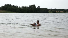Man teaching girl how to swim. - stock footage