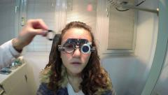Beautiful young female patient having a medical examination at optician Stock Footage