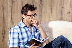 Man yawning while reading literature on couch Stock Photos