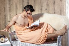 man reading on couch when alarm clock rings - stock photo