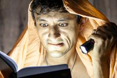 man reading novel book with flashlight under blanket - stock photo