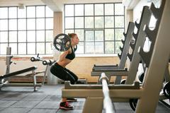 Fitness female doing squats in gym Kuvituskuvat