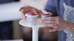 Girl puts cupcakes on a dessert stand tray for wedding or bakery Stock Footage