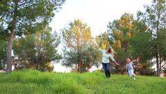 Mother and little son running across the green park Stock Footage