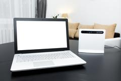 Laptop with blank screen and wireless internet router on the table Stock Photos