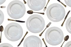 Pattern of vintage dinner plates, knives, forks and spoons - stock photo