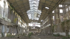 Ruined factory building with pile of armature blocks, weeds in hall, tilt down. - stock footage