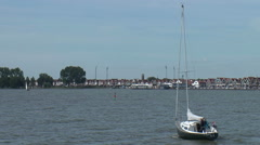 skyline and boat passing Volendam harbor traditional old dutch fishing village  - stock footage