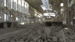 Ruined factory hall with fallen armature and concrete blocks, pan right. Stock Footage