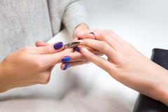 Beautician trimming cuticles of female client Stock Photos