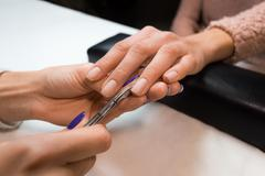 Removing the cuticle by manicure nippers - stock photo