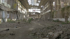 Ruined old building with fallen armature and wild bushes in hall,tilt up,indoors Stock Footage